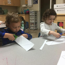 Children cutting paper with scissors