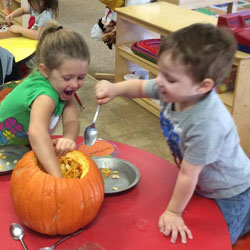 Children preparing a pumpkin for carving